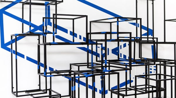 Black metal frames in cube shapes against a white and blue background