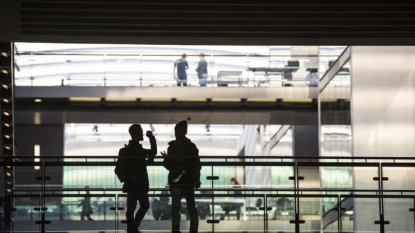 Silhouette of two people standing on a walkway