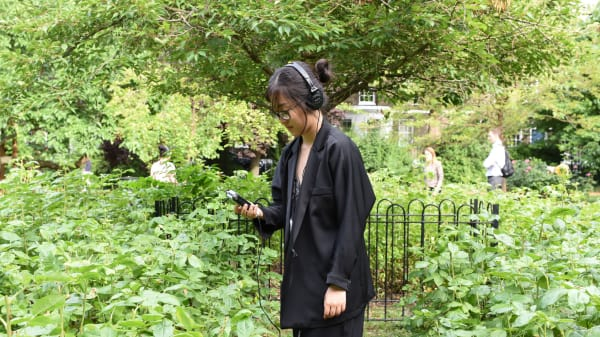 Woman walking through a garden wearing headphones looking at her phone
