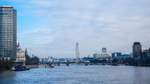 A wideshot of the River Thames and buildings of London against a blue sky