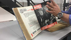 Photo of a man's hand turning the page of a hardback book on a stand