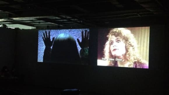 Photo of two cinema screens next to eachother. One with the back of a woman's head on with her hands up and the other with a woman facing the audience