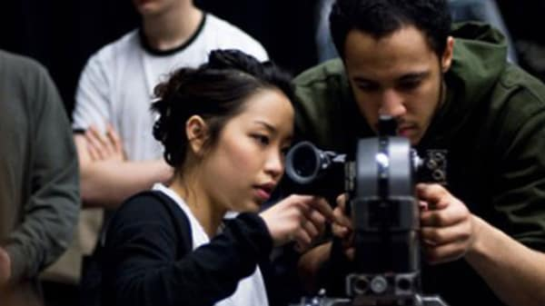 Photo of a man and a woman looking at a video camera
