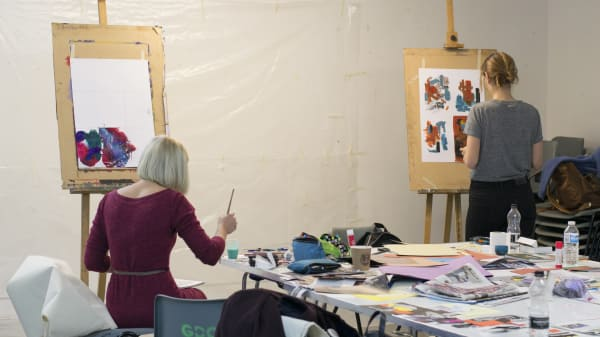 Students painting at easels in the art studio
