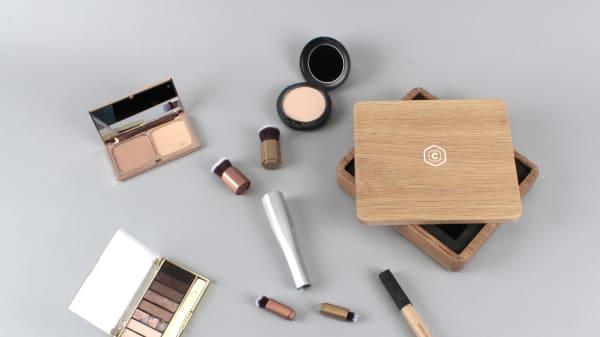 A flat lay of make-up, make-up tools and a wooden box