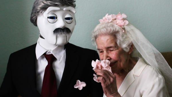A robot wearing a suit stood next to a woman wearing a wedding dress