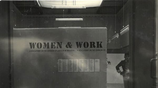 Archive image of a person stood next to an exhibition signs which reads 'Women & Work'