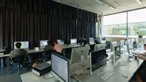 a room full of computers with students working