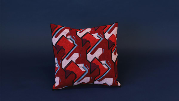 Pink and red cushion with blue and maroon detailing on a navy background
