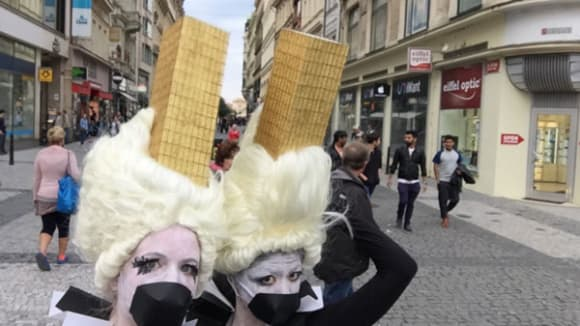 Photo of two women wearing ice cream cone costumes on their heads with black circles fixed over their mouths and black and white colours on