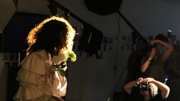 Student and model working in photography studio.