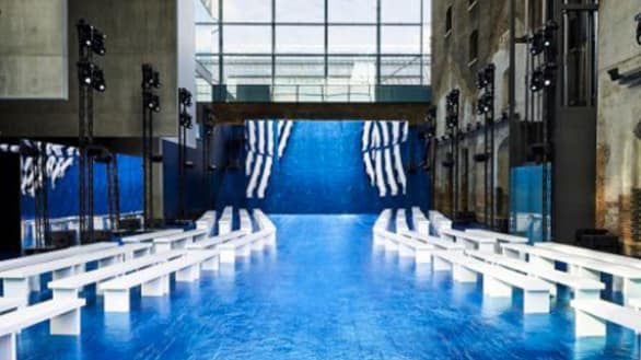 A blue runway with white benches on either sides