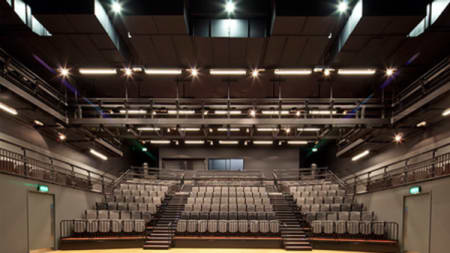 Photograph from the stage of the Platform Theatre looking out onto rows of grey seats.