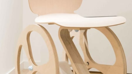Partial image of a wooden wheelchair made from light coloured wood which makes it look more aesthetically pleasing than normal