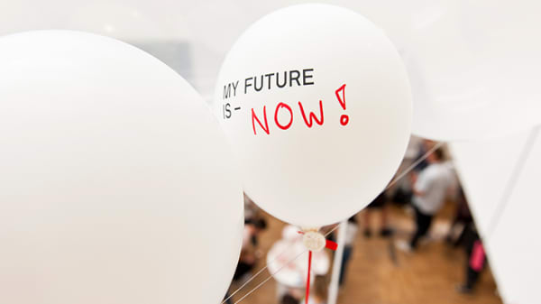 A white balloon floats with the text, my future is now, written on it.