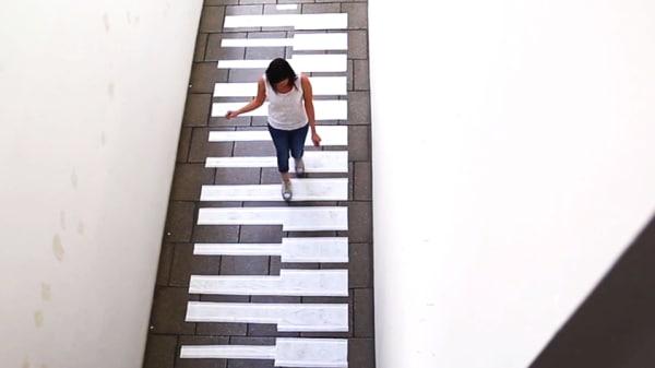 A lady walks across a melody piano down a corridor
