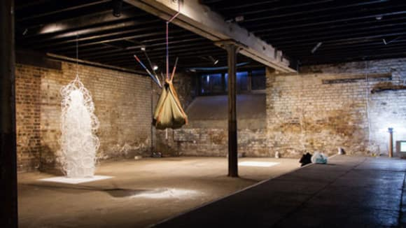 Photo of a large room with brick walls with a brown sack hanging from a beam and a white sculpture