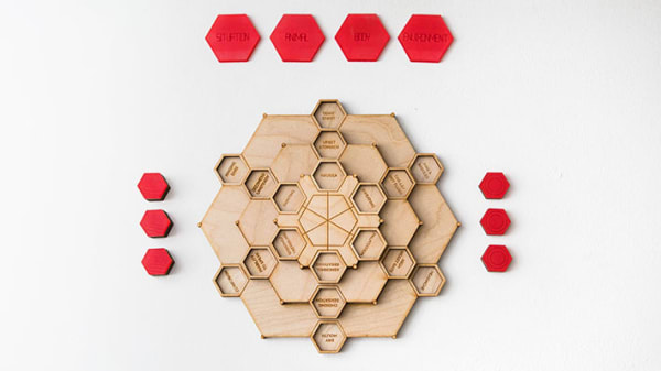 A wooden hexagonal game, the play pieces are red.