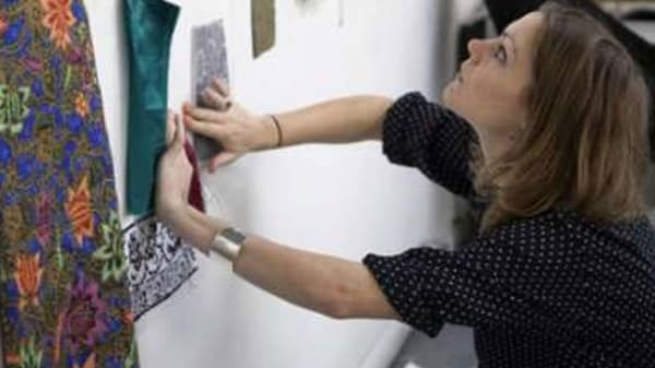 Photo of a woman hanging a piece of art work on a white wall