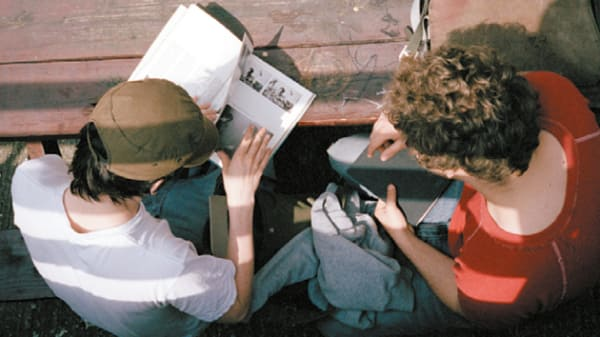 Two students reading reference books