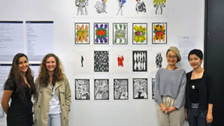 Four women stood either side of a collection of illustrations displayed on a wall