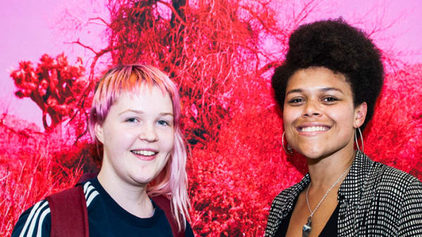 Two women stand in front of a red and pink artwork.