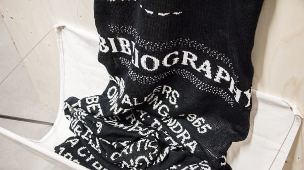 A woven material which is black with white words woven into it