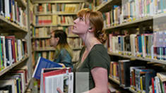 Photo of a woman holding books, looking at a bookcase