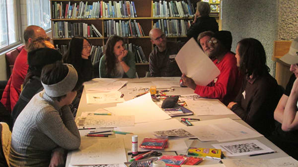 Photo of a group of people sitting around a table with pieces of paper on it