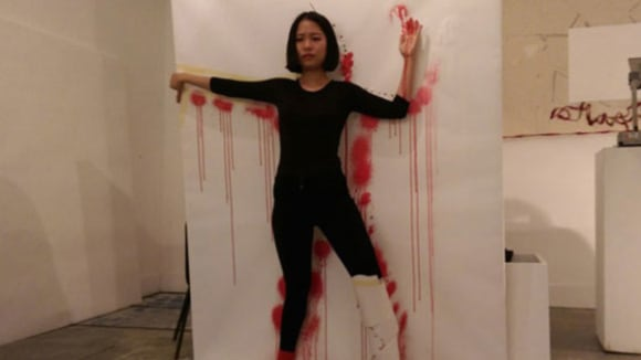 Photo of a woman dressed in black standing against a white wall with her arms up and red marks around her outline