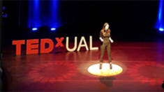 Photograph of a woman on a stage in front of a TEDxUAL sign