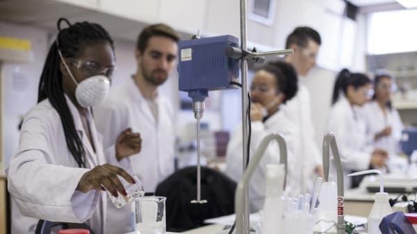 Cosmetic Science students from London College of Fashion in a lab.In the foreground a person is pouring clear liquid into a glass beaker.
