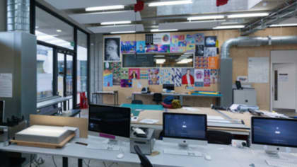 A wall filled with printed posters in front of which is a row of desks each with a computer