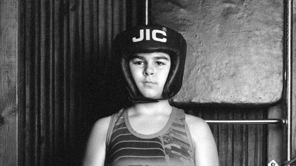 A photograph of a young person wearing clothes and accessories for boxing