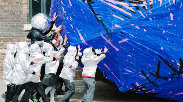A performance piece, a group of people wearing silver costumes pushing a large blue and pink shape through Granary Square