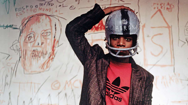 Photo of Jean-Michel Basquiat standing in front of a white wall with drawings on, wearing a helmet with one hand on his head