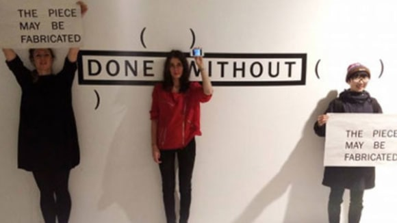 Photo of three woman standing in front of a white wall with 'done without' written on it and holding signs saying