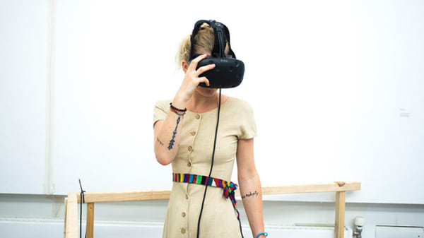 A blonde-haired woman raises her tattooed arm to the virtual reality headset she is wearing.