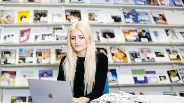 A young blonde woman sits at a desk working on her laptop