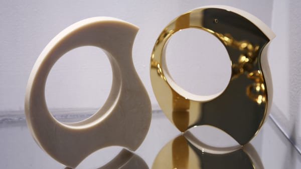 White and gold circular sculptures with a hole through the middle