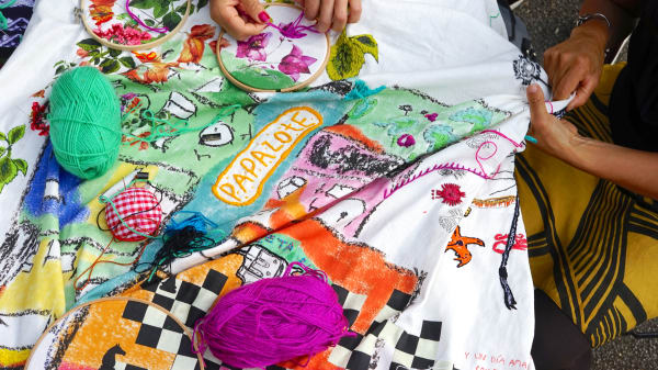 A bird's eye view of two people embroidery a large piece of decorative fabric