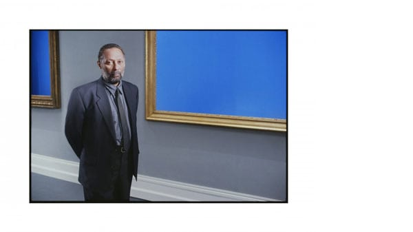A man stood in front of a blue panel in a gold gilted frame