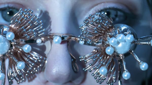 Close up of female model's eyes wearing gold flower shaped glasses with pearls on