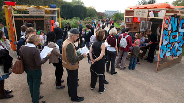 Photo of a group of people queueing outside a booth