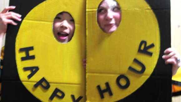 Photo of two people holding up pieces of card with a yellow circle on with cut out slots for their faces and 'happy hour' printed on it