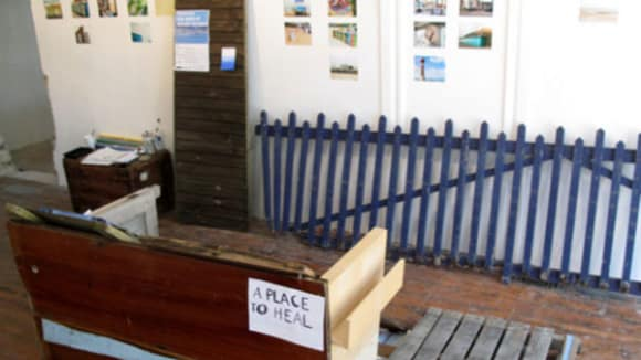 Photo of a room with a blue fence leaning against the wall as well as am upturned desk with a sign on saying