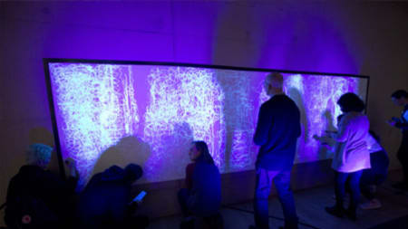 People appearing to paint in light on a screen in a darkened room