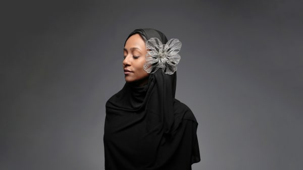 A person wearing black with a decorative silver flower