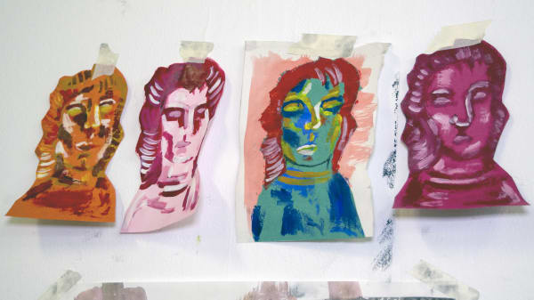 Four painted heads on the studio wall