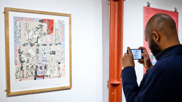 A man taking a photo of a piece of art hung on a wall